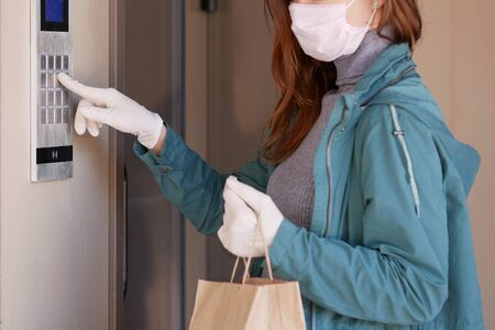 Couriers hands in black medical gloves deliver parcels in paper bag to the door during the epidemic coronovirus, COVID-19. Safe delivery online orders during epidemic.