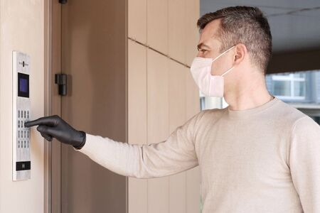 Man in face mask and gloves dials the code on the intercom and going in porch of his apartment. Pandemic covid-19 concept Foto de archivo
