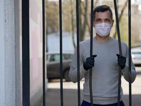 A man in white protective face mask near metal fence. Quarantine. Coronavirus concept. A man wearing protective mask and gloves
