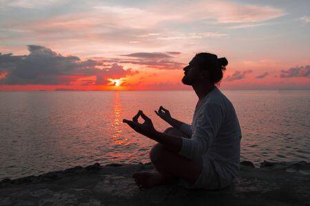 Yoga scene silhouette man in sunset. Ocean.