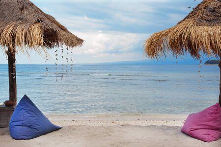 Straw umbrellas and bean bag at the seashore.