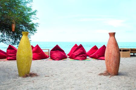 Red bean bags on the sand beach in Bali, Indonesia. Stock image.