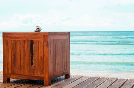 The table on the wooden deck overlooking the ocean and blue sky. Stock image.