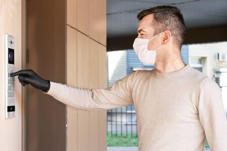 Man in face mask and gloves dials the code on the intercom and going in porch of his apartment. Pandemic covid-19 concept Stock Photo