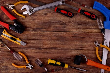 This is an overhead photo of construction tools and brush with copy space on a wood background. There is a lot of space Stock Photo