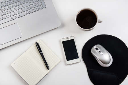 Cup of coffee and laptop on white table.