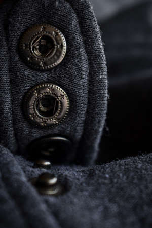 Close up view of woolen sweater cloth with vintage metal button