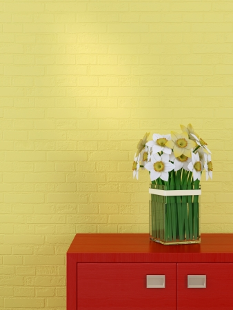 Beautiful daffodils and red chest of drawers against the background of yellow wall photo