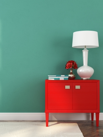 lamp: Stylish red chest with white table lamp and decoration on background of blue wall Stock Photo