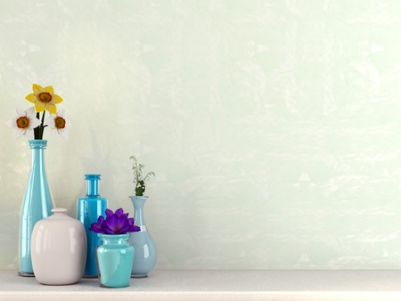 Beautiful glass vases with spring flowers against a green wall photo