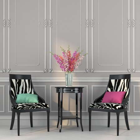 Two beautiful chair with fashionable prints and a black table with flowers 스톡 콘텐츠