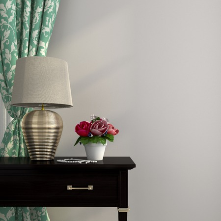 The elegant lamp with gilded basis stands on a table of dark wood and complements a composition the turquoise curtain