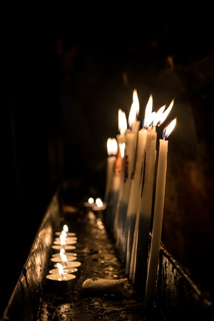 varying: The candles of varying heights burning in the dark temple Stock Photo