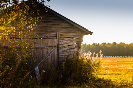 The autumn sun warms up the walls of the old barn house in the rural Finland.