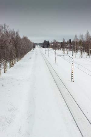 railroad track: The snowy railroad track leads to the horizon at the rural Finland.