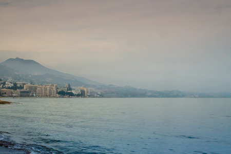 away from it all: View to a Mediterranean sea at Fuengirola, Andalusia, Spain.  The mountains shadow the beach hotels.