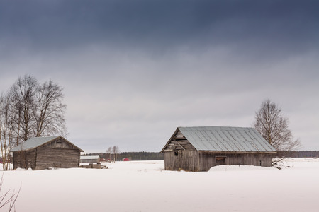 emphasizes: The white snow emphasizes the grey color of the old barn houses. They look very sad and abandoned in all that white surrounding them.