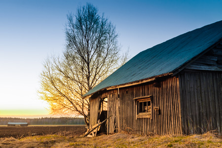 abandoned warehouse: This seems to be an old abandoned warehouse or shelter once used for machinery or as a workshop. Now the spring sunset colors the building orange. Stock Photo