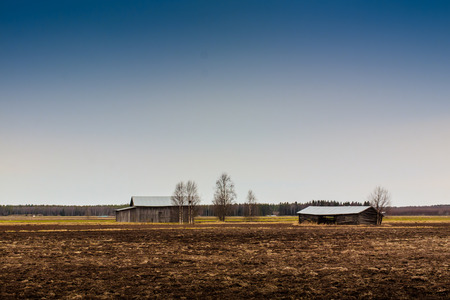 not ready: The barns on the spring fields are empty and waiting for the autumn to be filled with crops. These barns are not actually used any more but the look like they are ready for the work they were built for. Stock Photo