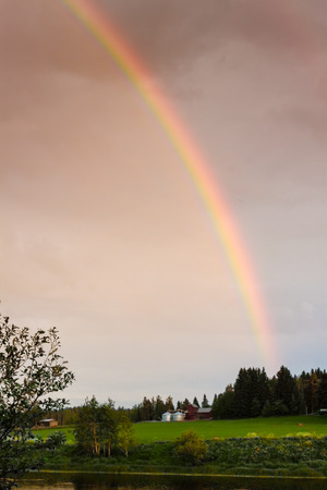 emphasized: The rainbow was as full as can be on a rainy night in the rural Finland. The sun was just setting and the sunset emphasized the colors beautifully.