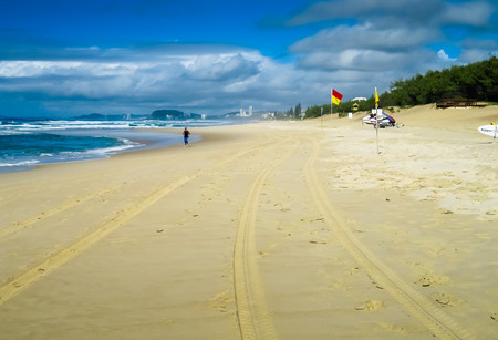 qld: A lonely jogger on the beach at the city of Gold Coast, QLD, Australia. Stock Photo