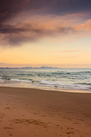 coolangatta: The city skyline seen from the town of Coolangatta in Queensland, Australia.  Note the beautiful flowers drawing on the sand. Stock Photo