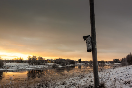 telephone pole: An old birdhouse attached to the telephone pole against the sunrise in the Northern Finland. Stock Photo