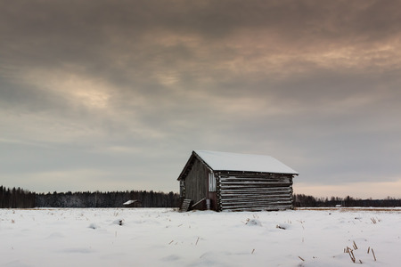 barns winter: The sun rises late in the middle of the winter in the fields of the Northern Finland. Stock Photo