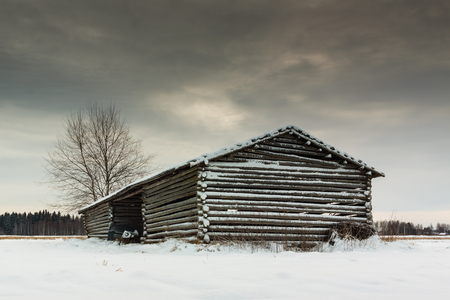 old barn in winter: This old barn house seems to have two parts combined only with a thin roof. The field is in the Northern Finland. Stock Photo