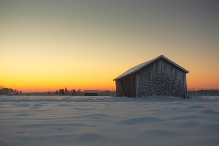 very cold: Barns on the fields on a very cold but beautiful morning in the Northern Finland.