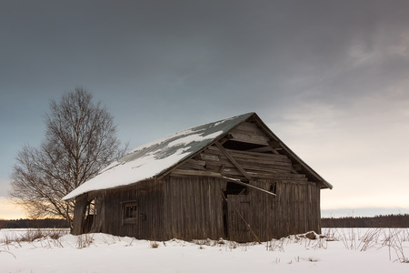 better days: The sun sets behind the old barn house in the Northern Finland. The barn has seen better days. Stock Photo