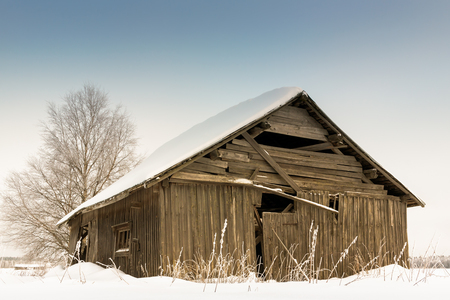 old barn in winter: The sun shines brightly in February and lights up the barns and the fields of the Northern Finland.