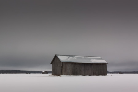 old barn in winter: Three old barn houses on a field covered with snow. The sky is grey on the winter day in the Northern Finland. Stock Photo