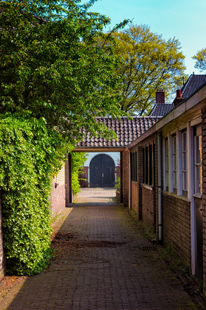 residental: A blue double door at the end of a narrow corridor in a pittoresque residental area in the town of Bussum, the Netherlands.