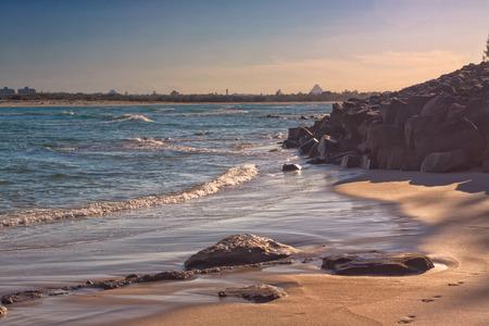 tu puedes: El sol de la tarde arroja sombras largas en la arena de una playa en Caloundra, Queensland, Australia. Se puede ver las montañas de invernadero en el fondo.