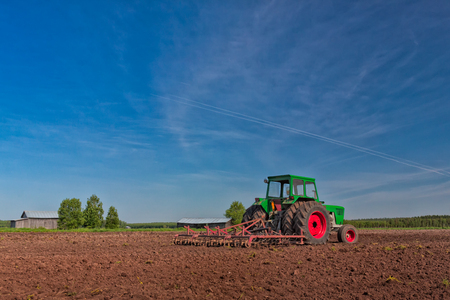 machinery space: The farmer is on a break on a beautiful early summer day in the Northern Finland. He has left his old tractor alone on the fields.