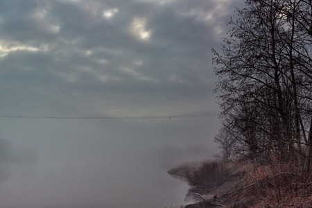 covered fields: A foggy night by the river Pyhajoki in the Northern Finland. The mist rising from the water and the fields has covered everything in sight. Stock Photo