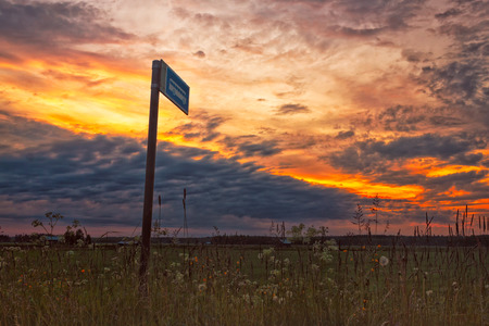 A lonely bus stop in the middle of the fields in the rural Finland. It is midsummer and the sun hardly sets. However, the sunset creates dramatic skies with the clouds.