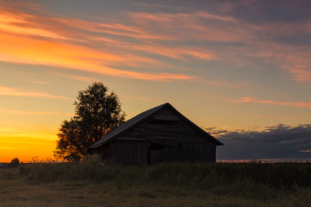 The midsummer sun sets beautifully behind and old barn house in the Northern Finland. It's almost the nightless night. Stok Fotoğraf