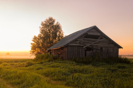 A lonely barn house on a very misty field during the midsummer sunset. The sun hardly sets in the rural areas of the Northern Finland in the summertime. Stock Photo