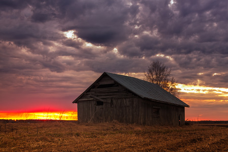 quite: The April sun sets behind an old barn house in the rural Finland. The nights are already quite white in the late spring. Stock Photo