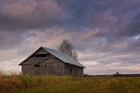 quite: The autumn days in the Northern Finland tend to be quite gray. Sometimes the sun peeks through the clouds and lights up the old barn houses. Stock Photo
