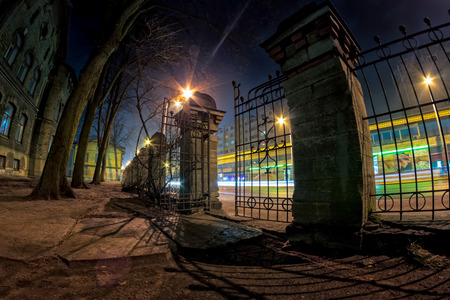 An old iron gate in Tallinn, Estonia. It separates and old garden and one of the busiest streets in the city.