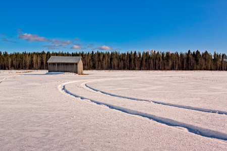 Tracks on the snowy field in the Northern Finland. I dont know what kind of vehicle has left the tracks, maybe a tractor. Stock Photo