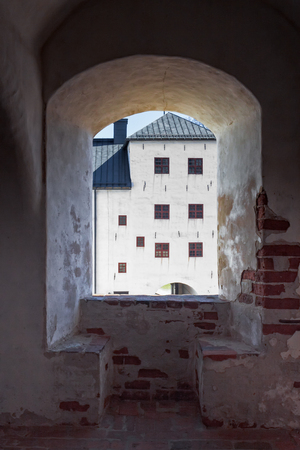 One of the buildings of the Turku castle seen through an old window. The castle is medieval and it has many buildings built in different eras.