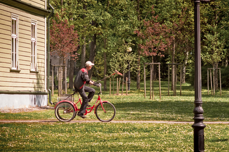 A park worker riding a tricycle at the Kadriorg park in Tallinn, Estonia. Hes carrying a rake, too. Maybe his looking for dead leaves.