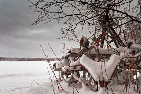 An old farming equipment has been covered by the nightly snowfall in the Northern Finland. Winter came surprisingly quickly this year. Фото со стока