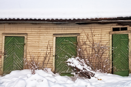 Three green wooden doors on an old building in the Northern Finland. The patterns of the doors are very typical in these parts of the country. The building has seen better days and the doors are not e