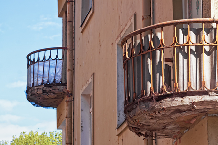 Two old balconies are hanging on the wall of an old building in Tallinn, Estonia. They have been supported somehow, but they look like they will fall any second now. 写真素材