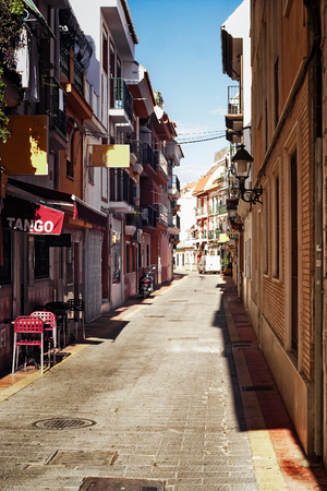 A small tavern is advertizing tango on a narrow alley in Fuengirola, Spain. The town is bathing in the midday sun. Editorial